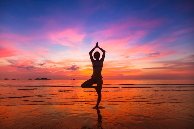 Silhouette of woman practicing yoga during sunset at the seaside